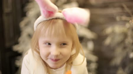 havuç : Baby girl in white costume of rabbit eats a carrot among christmas decorations. Stok Video