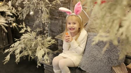 kostüm : Baby girl in white costume of rabbit sits among christmas decorations and eats a carrot.