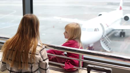chegada : Mother and daughter are looking through the window at a aircraft that came to departure gate. Vídeos