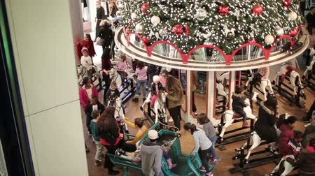kolotoč : Time lapse. Fast motion. Many people ride on the carousel on horseback. Holidays in the mall.