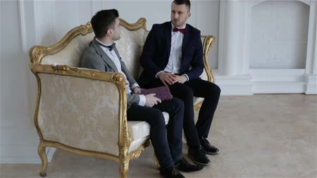 plated : Two businessmen in suits with bow ties are communicating in a beautiful white room with elegant gold sofa.