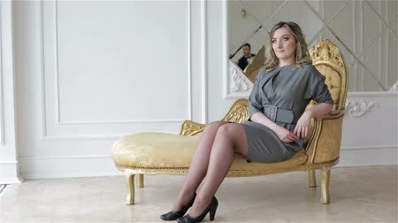 make photo : A woman model in grey dress is sitting on the golden chair in studio.