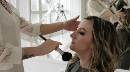 kartáč : Womans hands with a cosmetic brush are applying makeup to the model face.