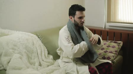 başörtüsü : A man in a white gown comes into the room, puts on a scarf and lies down.