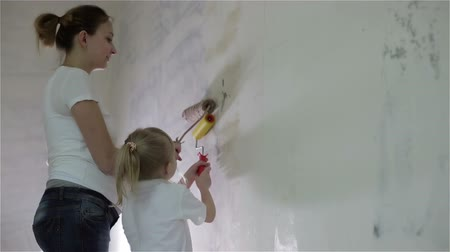 zeď : A pregnant mother and a small daughter painting a wall with rollers.