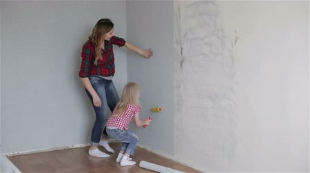 malarstwo : A mother and a small daughter applying a paint roller. Wideo