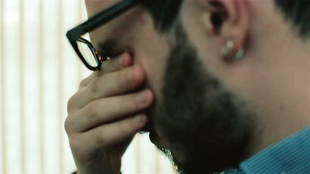 eyes closed : A man in glasses rubbing his eyes and talking. Stock Footage