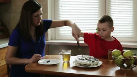 mutfak : Mom is helping young son to cut the cake.