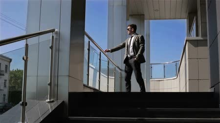 ношение : Businessman is coming out of the business center and standing on the porch leaning on the railing. Стоковые видеозаписи