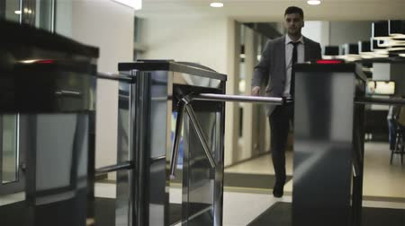 hozzáférés : The businessman is passing through a turnstile.