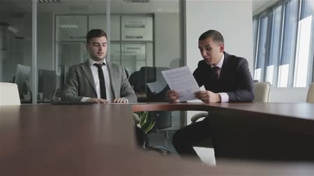 jurist : Businessmen in suits and ties discuss a case sitting at a table. Stock Footage