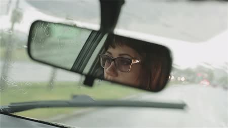 носить : A woman in glasses driving in rain.
