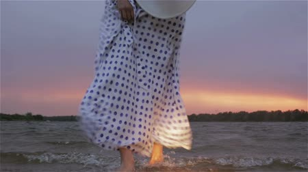 ветер : Girl in white dress walks barefoot in the water at sunset. Стоковые видеозаписи
