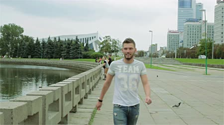 looking towards : A young bearded man jumps from the concrete fence of the river and walking along the sidewalk. Stock Footage