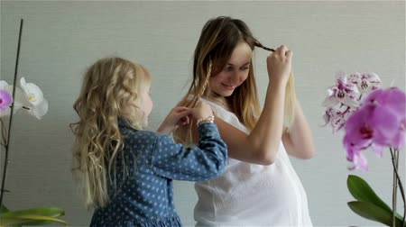 braid hairs : Little blonde daughter is plaiting pigtail from her mothers hair.
