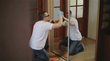 glass master : Man standing on his knees and cleaning a mirror. Slow motion. Stock Footage