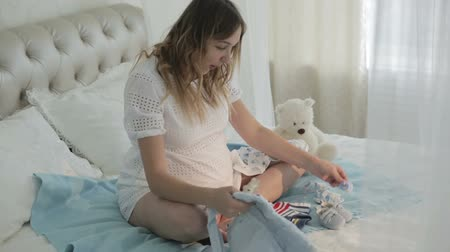 booties : Beautiful pregnant women in white dress looking at babies clothes.