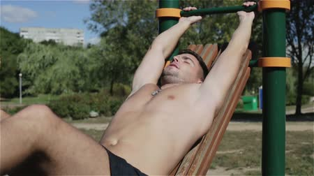 párhuzamos : Slow motion. The young man is training an abdominal muscles on the bars.