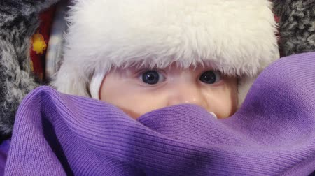 nipple : Child looks out from cozy winter cap. Stock Footage
