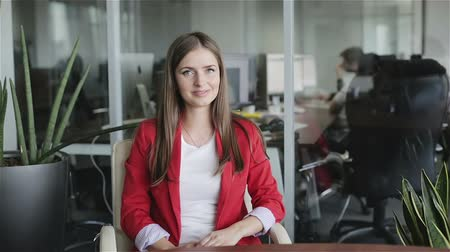 um : Beautiful business woman sitting at the desk in the office and talking.