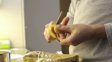 skins : Close up. Mans hand peeling potatoes with knife.