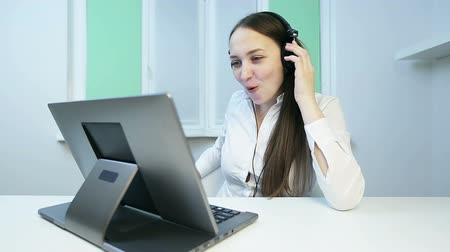 kötü : Attractive girl in headphones speaks on the video camera on the laptop.