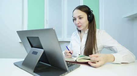 kötü : Young business woman with headphones carries a meeting on the video call.