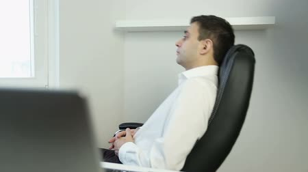 rubs : Young businessman finishing typing on a laptop and resting on an office chair.