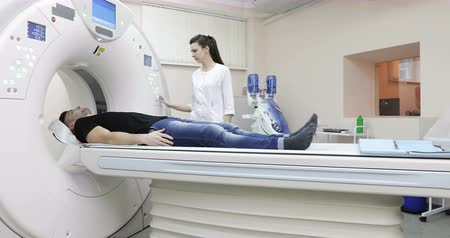 tomograph : 4K Young caucasian male gets scanned by magnetic resonance imaging scanner in modern hospital. Stock Footage