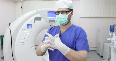 tomograph : 4K A young doctor radiologist in a mask corrects medical gloves. Stock Footage