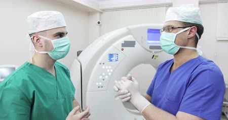 tomograph : 4K Two young doctors in a mask discussing on a background of a new magnetic resonance imaging. Stock Footage