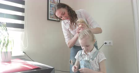 pigtailler : Attractive mother makes her daughter hairstyle. Stok Video
