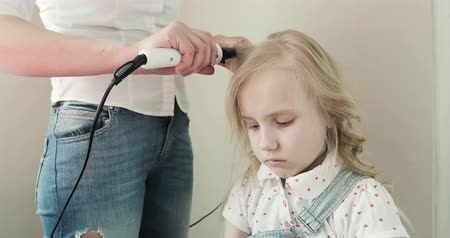 pigtailler : A young mother curls her sad daughters hair. Stok Video