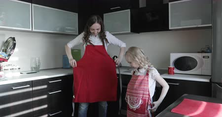 culinária : A young mother and her daughter putting on red aprons at the kitchen.