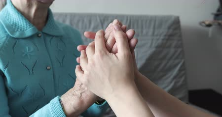 idősek : A young woman holds wrinkled hands of an old grandmother. Stock mozgókép