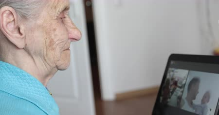 memórias : An elderly woman with gray hair looks at the photo on an electronic tablet. Vídeos