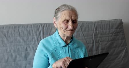 memórias : Old woman and tablet pc.