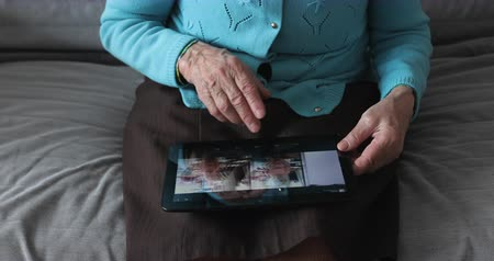 memórias : Hands of the old woman and electronic tablet.