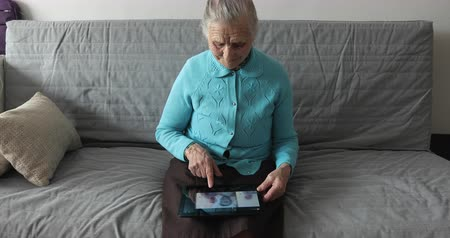 memórias : An old woman is sitting on the couch and using a digital tablet.