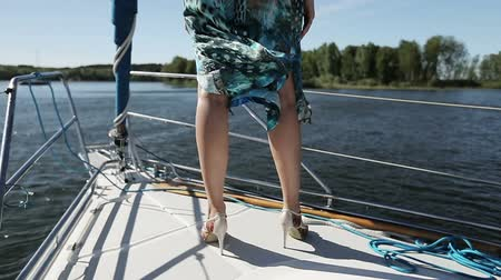 kudrnatý : Slender legs of a young girl in high heels on a yacht.