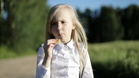 идущий : Hungry school girl in white shirt and black skirt is walking by the sandy road through the field and eats a biscuit.