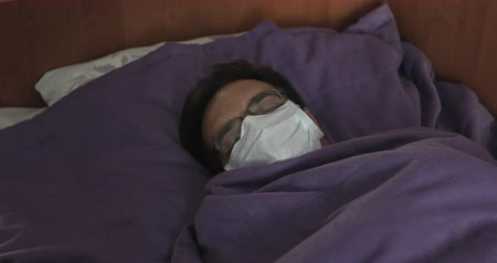estilização : A sick man in a white mask lies in bed in the clinic during an infection. Epidemic.
