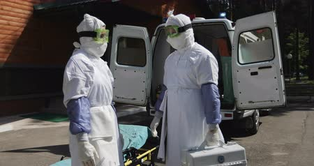 suspected : Two unrecognizable doctors or nurses wearing full Ebola virus protection uniform  standing near ambulance car and talking.