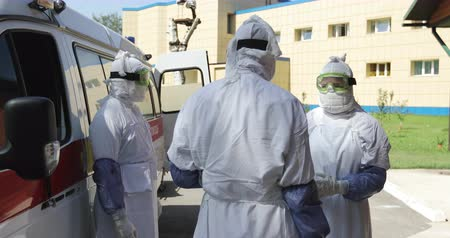 suspected : Three unrecognizable doctors or nurses wearing full Ebola virus protection uniform  standing near ambulance car and talking.