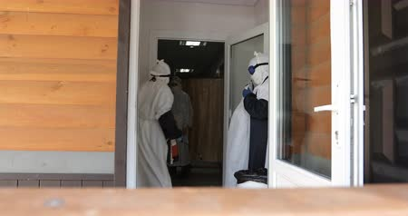 suspected : Doctor or nurse wearing full Ebola virus protection robe waiting for patient near the door.