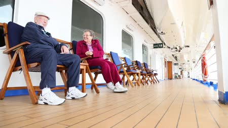 személyszállító hajó : Pan of a Loving Senior Couple Relaxing and Talking on the Deck of a Luxury Cruise Ship.