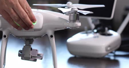 uav : Pilot Turns On Drone Quadcopter With Controller Behind