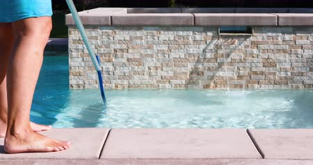 4k Looping Seamless Cinemagraph of Woman Skimming Swimming Pool Water.