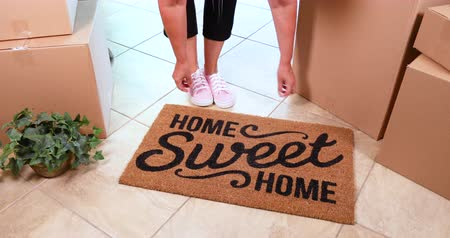 Couple Moving Into New House Laying Down Home Sweet Home Welcome Mat and Boxes
