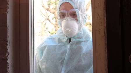 hazmat : Control of epidemic and pandemic-prone acute respiratory diseases. Personal protective equipment. A man knocks on the window Stock Footage